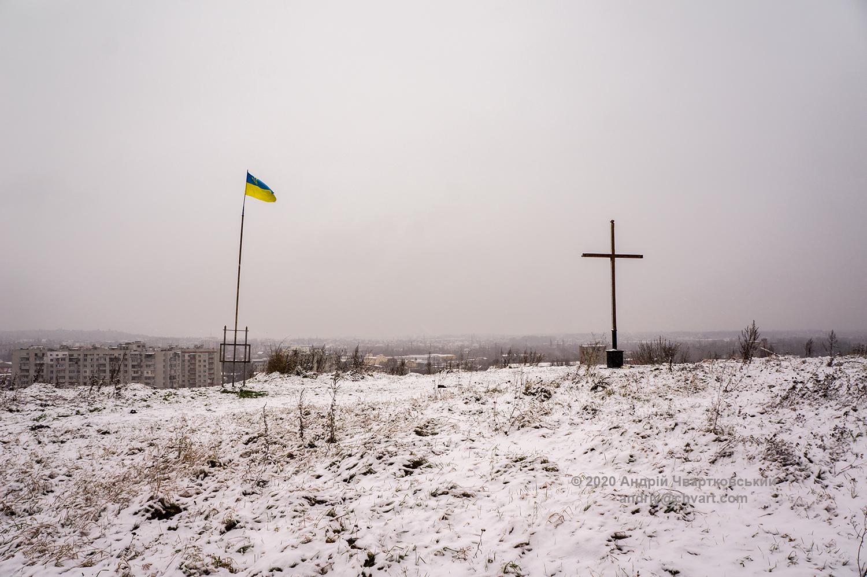 Український прапор і хрест на плато гори